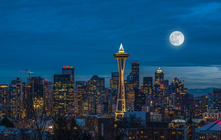 The lights come on in Seattle with a full moon at night