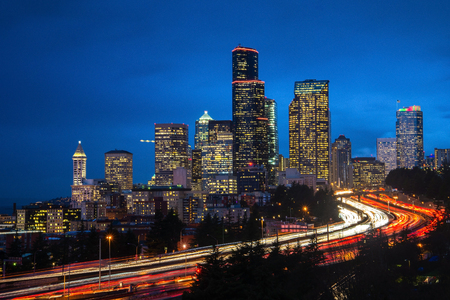 Seattle skyline at hour traffic with light trails.