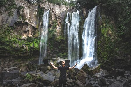 Man enjoying waterfall raised hands