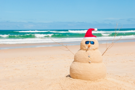 christmas in july: Snowman on holidays made out of sand instead of snow. Concept could be used for Global Warming & Christmas Cards