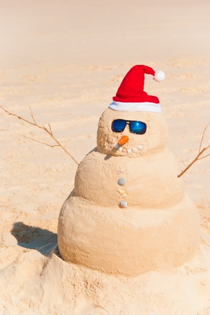 christmas in july: Sandman with santa hat, carrot nose and sun glasses on the beach. Global Warming Concept Stock Photo