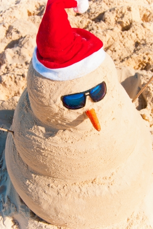 christmas in july: Birds Eye View On Snowman With sunnglasses and carrot nose on beach