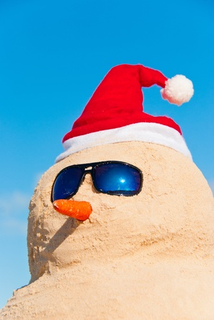 christmas in july: Funny Christmas Character made out of sand wearing santa hat sun glasses and has carrot nose. Copyspace in blue sky. Global Warming concept