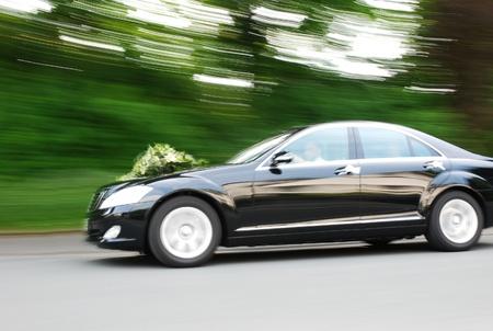 Elegant bridal car speeding with flowers on hood. Motionblur