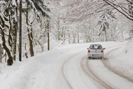winter road: Driving with bad weather conditions: road is covered by snow