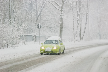 slowdown: Driving with bad weather conditions: road is covered by snow