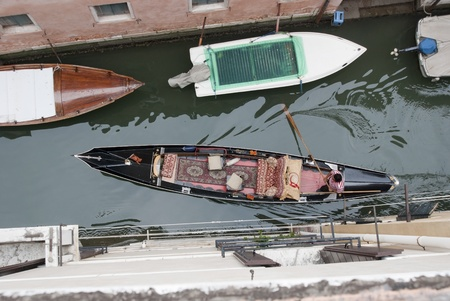 Birds eye view on gondola in narrow canal, venice, Italy, Europe. Boats are the daily traffic in this famous city. Watch out for the shape the paddle creates in the water