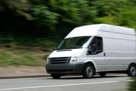 Weißer Lieferwagen mit Motion blur auf Straße mit grün / Bäume im Hintergrund