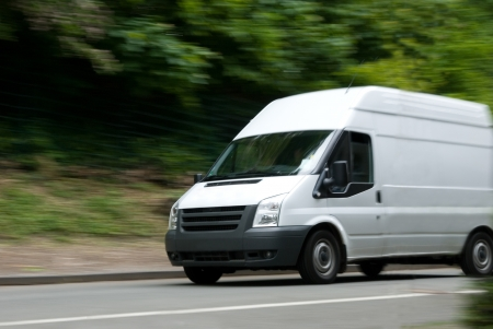 delivery van: White delivery van with motion blur on street with green  trees in background Stock Photo