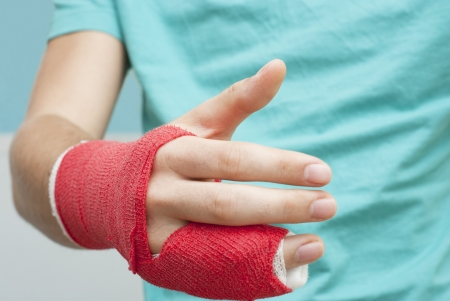 Injured male hand with upper part of body. Hand is bandaged with red plaster focus set on thumb photo