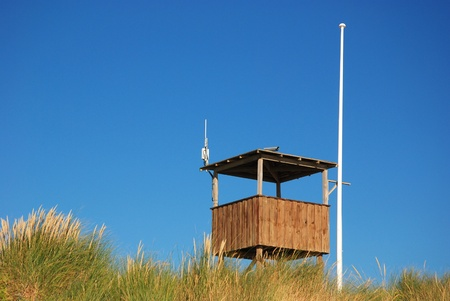 Wooden stand and flagpost against blue sky behind dune photo