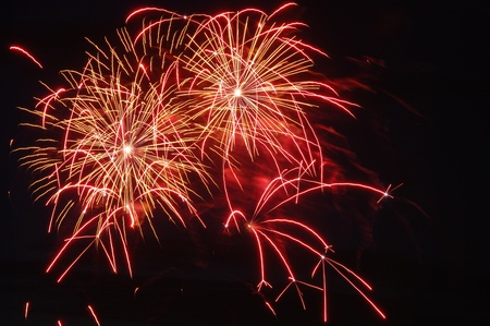 Firework sparkles in red and yellow on dark sky. Stock Photo - 10336486