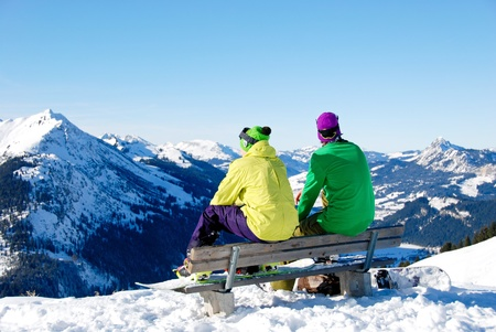 snow break: Two young men sitting on a bench on top of a mountain. They have a break after a snowboard session. Stock Photo
