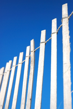 stockade: woodenfence on dune at beach bleached from sun against blue sky