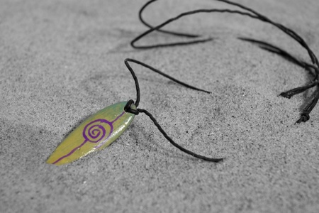 Small Surfing necklace on beach photo