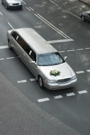 wedding limousine with traffic on urban road. The streched car has a bouquet on its hood photo