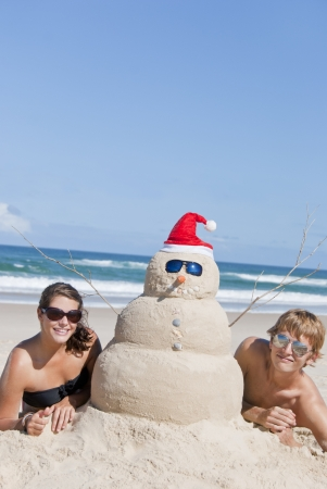 Pretty couple having fun at beach with perfectly build snowman made out of sand. With sunglasses and copyspace in the blue sky Imagens
