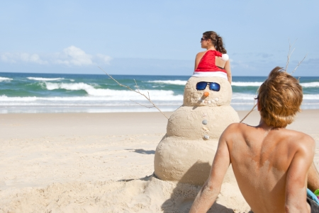 vegetables young couple: Pretty couple having fun at beach with perfectly build snowman made out of sand wearing sunglasses Stock Photo
