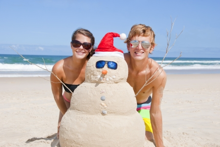 sandcastle: Pretty couple having fun at beach with perfectly build snowman made out of sand. With sunglasses, carrot nose and shells as buttons and mouth and santa hat. Stock Photo
