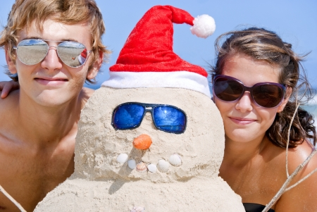 Pretty couple having fun at beach with perfectly build snowman made out of sand wearing sunglasses Imagens