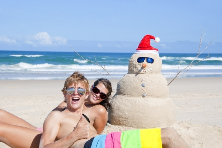 Pretty couple having fun at beach with perfectly build snowman made out of sand wearing sunglasses photo