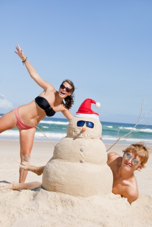 Pretty couple having fun at beach with perfectly build snowman made out of sand wearing sunglasses Reklamní fotografie