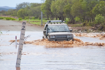 4wd: 4x4 is slowly crossing flooded road next to a mark indecating waterlevel.