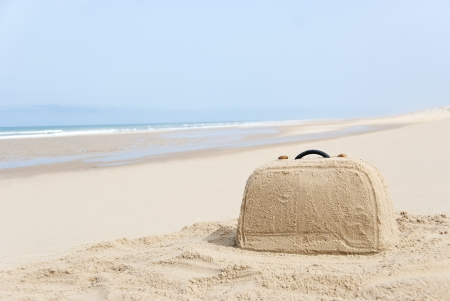 Suitcase on remote beach made out of sand. There is loads of space for your writing photo