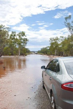 Car next to flooded road waiting untill waterlevel drops. Captured during rain season in Western Australia
