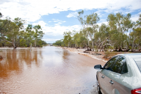 FLOODING: Car next to flooded road waiting untill waterlevel drops. Captured during rain season in Western Australia