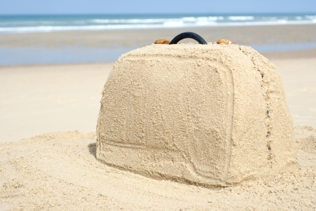 loads: Suitcase on remote beach made out of sand. There is loads of space for your writing
