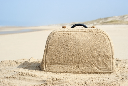 Suitcase on remote beach made out of sand. There is loads of space for your writing on the baggage Reklamní fotografie