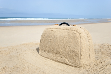 Suitcase on remote beach made out of sand. There is loads of space for your writing