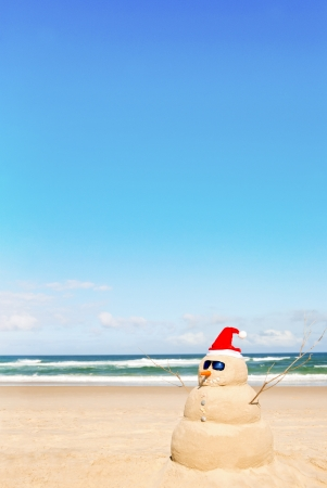 strand australie: Sneeuwman op het strand met schelpen als mond en zonnebril