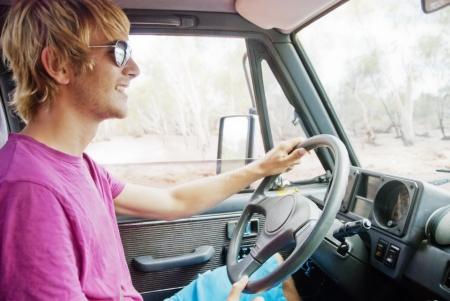 Young man with sunglasses driving car smiling photo