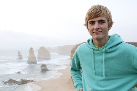 Young blond man with turquise at Twelve Apostles near Great Ocean Road Australia