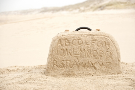 Suitcase with alphabet letters writing made out of sand on beach photo
