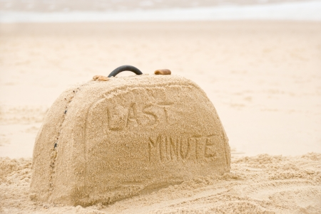 Last minute written on suitcase build out of sand on beach concept Imagens - 18842747