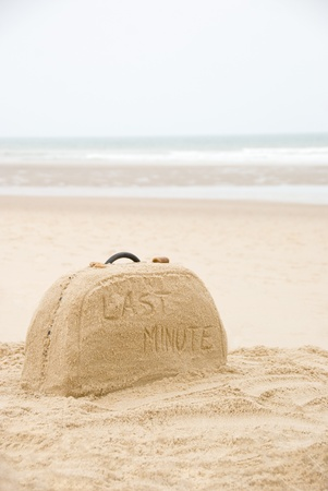 Last minute written on suitcase build out of sand on beach concept Stock Photo - 18842932