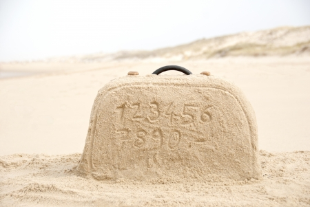 sand writing: Suitcase with numbers for price tag writing made out of sand on beach Stock Photo
