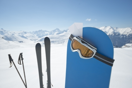 fee: Blank ski pass and winter sport equipment such as ski and snowboard waiting on top of mountain ready for you. Concept to illustrate ski admission fee