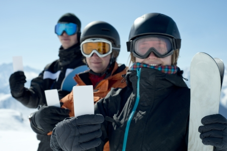 mount price: Winter sport friends showing ski lift pass smiling. Concept to illustrate ski admission fee