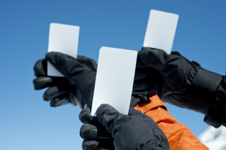 fee: Gloved hands holding lift pass against blue sky. Concept to illustrate ski admission fee