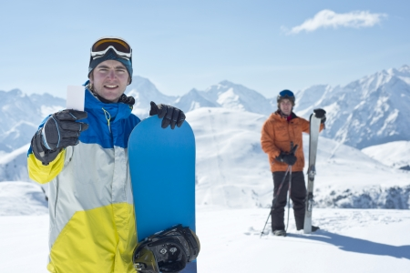 Two man with winter sport equipment looking at camera. One is showing a blank lift pass. Concept to illustrate ski admission fee Imagens - 20580188