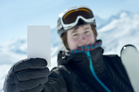 Winter sport girl showing bank lift pass. Concept to illustrate ski admission fee Reklamní fotografie