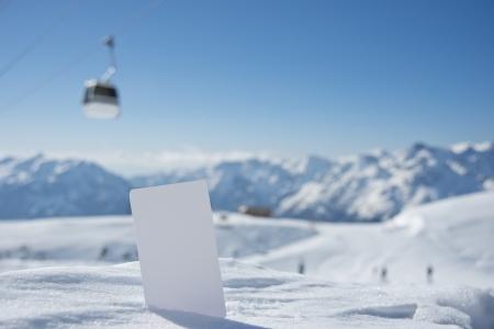 honorarios: Levante pasar la tarjeta en la nieve con borrosa gama telesilla y la monta�a. Concepto para ilustrar cuota de admisi�n Deportes de Invierno