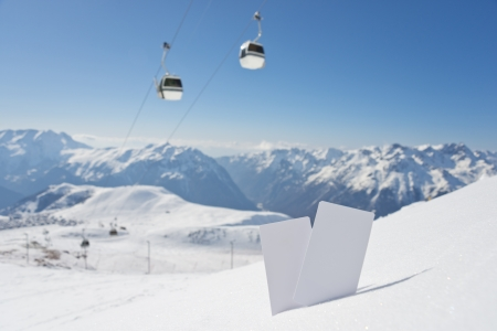 wintersport: Lift pass card in snow with blurred ski-lift and mountain range. Concept to illustrate Wintersport admission fee