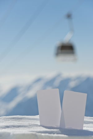 Lift pass card in snow with blurred ski-lift and mountain range. Concept to illustrate Wintersport admission fee