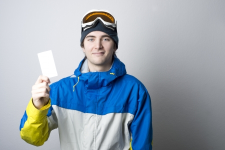 Young man holding blank ski lift pass looking. Concept to illustrate ski admission fee Imagens - 20580191