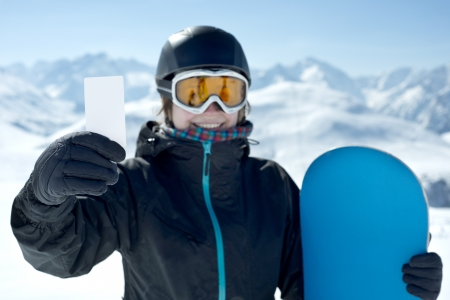 Winter Sport girl holding skipass and snowboard smiling. Concept to illustrate ski admission fee Reklamní fotografie